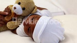 Baby boy lying in crib with teddy bear