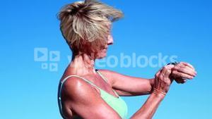 Fit senior woman pausing on her run to check her heartrate