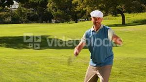 Man celebrating on the putting green of golf course