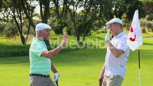 Man high fiving his friend after putting his golf ball