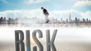 Businessman walking across tightrope with risk text