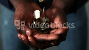 Man catching falling coins in hands