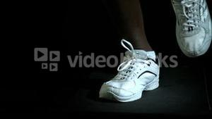 Legs in running shoes jogging against black background