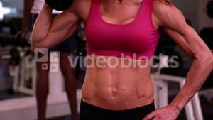 Super fit woman lifting dumbbells in pink sports bra