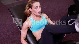 Super fit woman using the leg weights machine