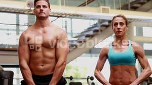 Two fit people lifting kettle bells together