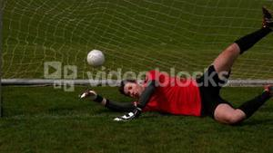 Goalkeeper in red letting in a goal during a game