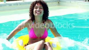 Gorgeous woman in swimming pool splashing in inflatable ring