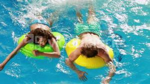 Couple swimming on inflatable rings in the pool