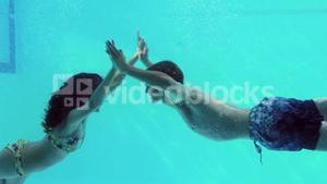 Happy couple jumping in swimming pool together holding hands