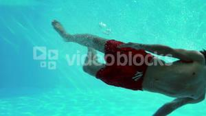 Happy man diving into swimming pool