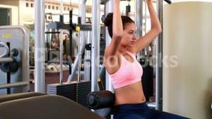 Fit brunette working her arms on the weight machine
