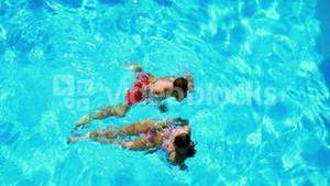 Happy couple swimming in clear blue pool