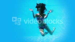 Pretty brunette swimming underwater in pool