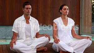 Calm couple in white sitting in lotus pose