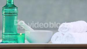 Towels and glass bottle with candle and mortar and pestle