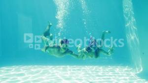 Happy couple jumping into swimming pool wearing snorkels and holding starfish