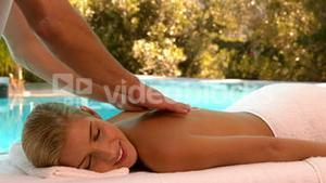Masseuse rubbing oil into blondes back poolside