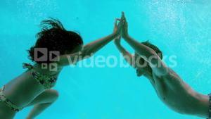 Happy couple holding hands underwater in swimming pool