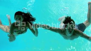 Happy couple holding hands underwater in swimming pool and waving