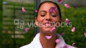 Beautiful brunette in bathrobe at the spa throwing up rose petals