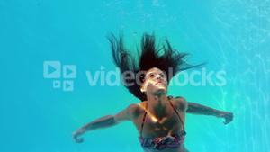 Brunette swimming underwater in the pool