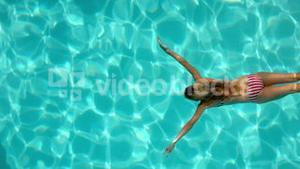 Woman swimming in the pool underwater overhead