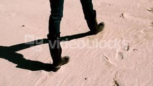 Woman in boots walking on the sand