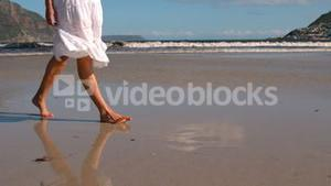 Woman in white dress walking on the wet sand