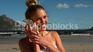 Smiling blonde listening to conch on the beach