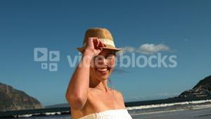 Smiling blonde taking off her sunhat on the beach
