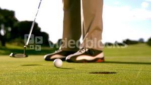 Golfer putting the ball on the green