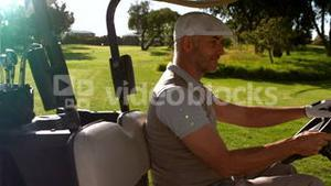 Happy golfer driving buggy on the golf course