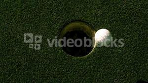 Golf ball rolling into the hole on putting green