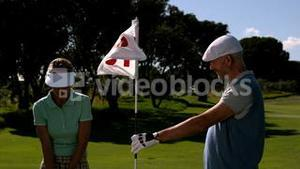 Smiling golfer holding eighteenth hole flag for his partner
