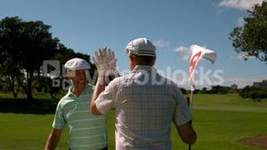 Golfers high fiving on the eighteenth hole