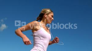 Fit blonde jogging and listening to music on sunny day