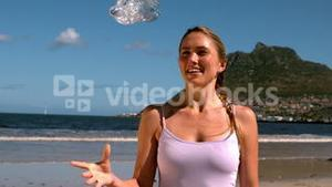 Fit blonde smiling and throwing her bottle on the beach