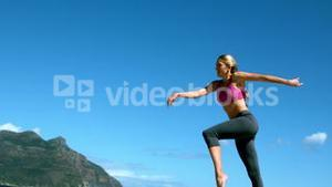 Fit blonde running and jumping on the beach