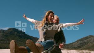 Carefree mature couple going for bike ride on the beach