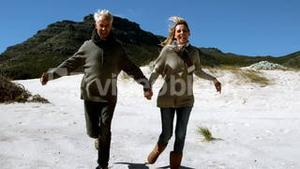 Carefree mature couple running holding hands on beach