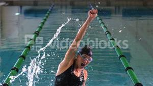 Fit swimmer jumping and cheering in swimming pool