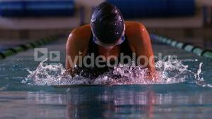 Fit swimmer doing the breast stroke in swimming pool