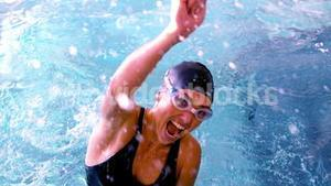 Fit swimmer jumping up and cheering in the pool