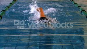 Fit female swimmer doing the front stroke in swimming pool
