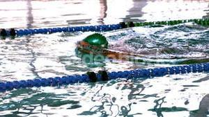 Fit swimmer doing the breast stroke in the swimming pool