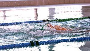 Fit swimmer doing the back stroke in the swimming pool