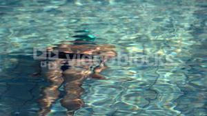 Muscular swimmer swimming underwater in the pool