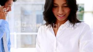 Businesswoman smiling and using a smart watch