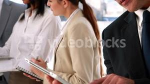 Business people standing and talking using tablet pc